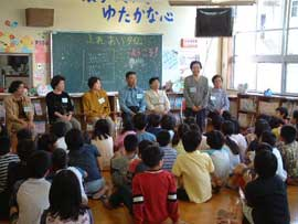 A group of school children gather in a classroom, listening to the stories of  older guests