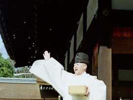 A priest in formal attire stands at the corner of a building, arm outstretched, throwing beans