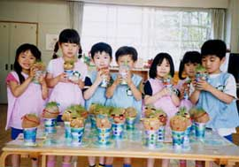 Seven preschoolers in smocks, pose in front of a table, holding gifts they have made