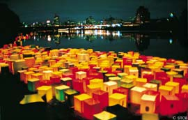 Hundreds of boxed lanters float on a river, with the city lights in the background