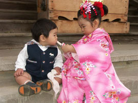 A young girl in a pink kimono gives candy to a younger boy in a suit