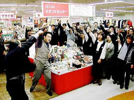 Department store workers gather around a display, cheering in unison, with one arm raised