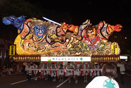 Dozens of people in matching white outfits carry colorful, illuminated floats at night