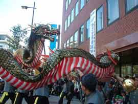 People maniuplate a large dragon on a narrow city street
