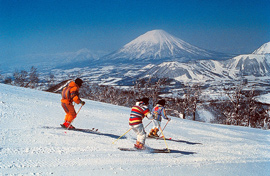 Three people skiing down a mountain, with Mt. Fuji in the background