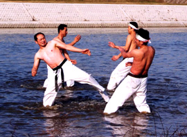 Four men without shirts, stand knee deep in a river, practicing martial arts