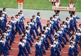People in matching colorful clothes marching in opening ceremony on a track