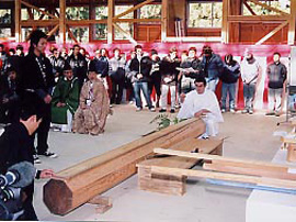 Workers watch as a priest keels over a piece of lumber.
