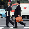 Two men in suits walking in a crosswalk.