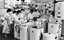 1950s photo of women looking at washing machines in store