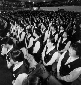 Auditorium filled with women in matching work uniforms