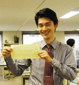 A man smiles while holding his paycheck.