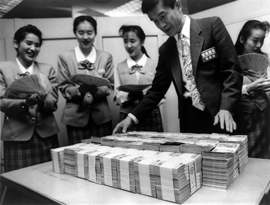 A man stands above bundles of cash while four women fan the cash they have received.