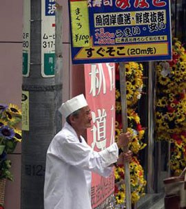 Older man standing against lightpost, holding a sign for a store