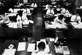 A group of workers at their desks while supervisor looks on from his desk in front