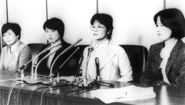 Four women at a table speak into microphones
