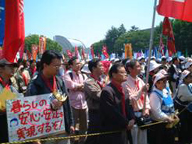 A large group of people gather outdoors while holding colorful banners and signs