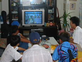 A group of boys sit facing the TV, playing computer games