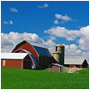 A barn and silo under a blue sky.
