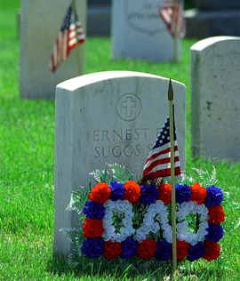 A gravestone with US flag and ribbons spelling Dad