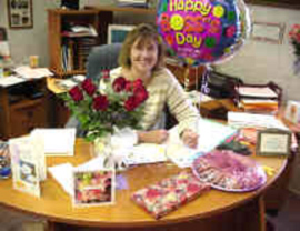 A woman at a desk, with flowers and balloon