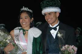 Boy and girl in formal clothes, wearing crowns.