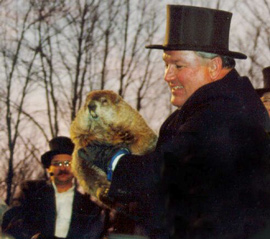 A man in a top hat holding a groundhog.