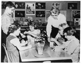 PTA mother standing at table with children sitting