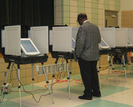 man standing in front of voting machine screen.