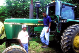 Two African American men stand by a green tractor.