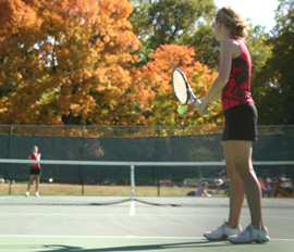 Gril playing tennis with fall colors in background