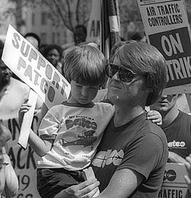 Striking air controler holds his son at a rally.
