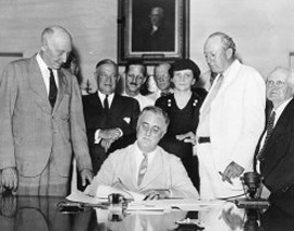 Roosevelt signs papers while seated at a table.