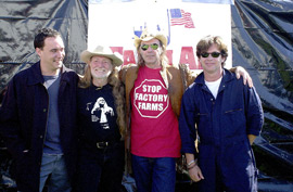 Four famous musicians stand in front of a tarp.