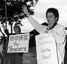 Two women hold signs supporting teachers.