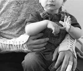 A man wearing wrist braces holds a child.