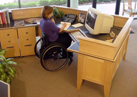 Wheelchair user in front of her compuer at desk