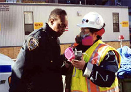 Person in hardhat and mask gives mask to policeman